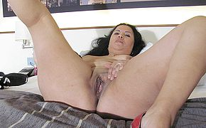 Nasty mature bitch toying on her sofa with a faux cock