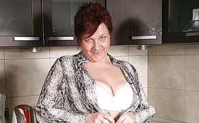 Big titted mature tramp frolicking in her kitchen